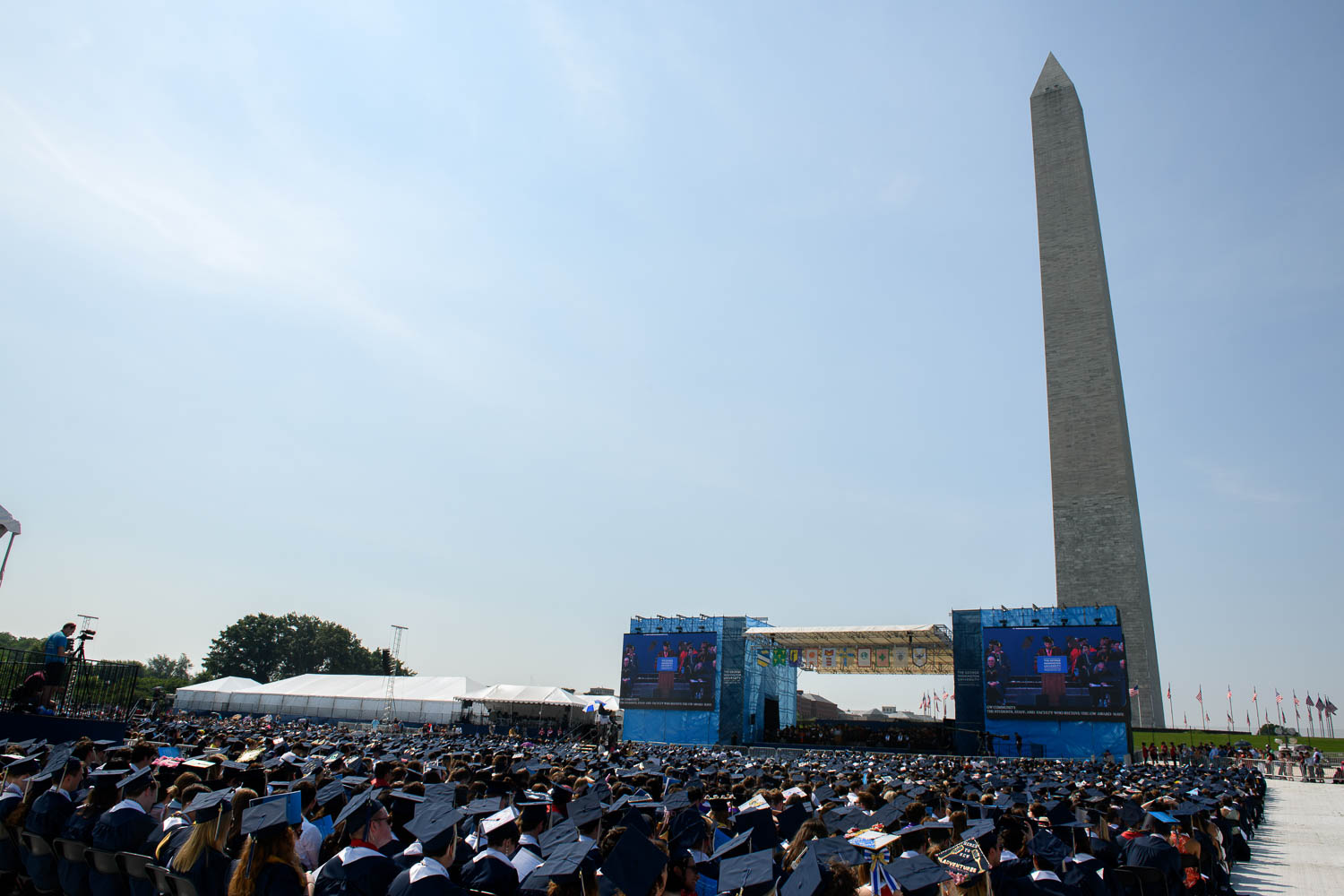 Washington Monument in background of Commencement stage with Guthrie speaking at podium