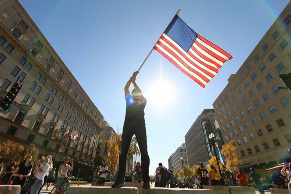 Image of a masked man waving an American flag.