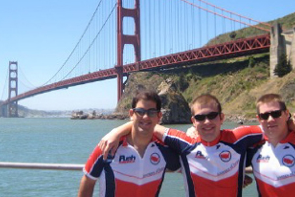 three bike riders with arms outstretched with Golden Gate Bridge in background