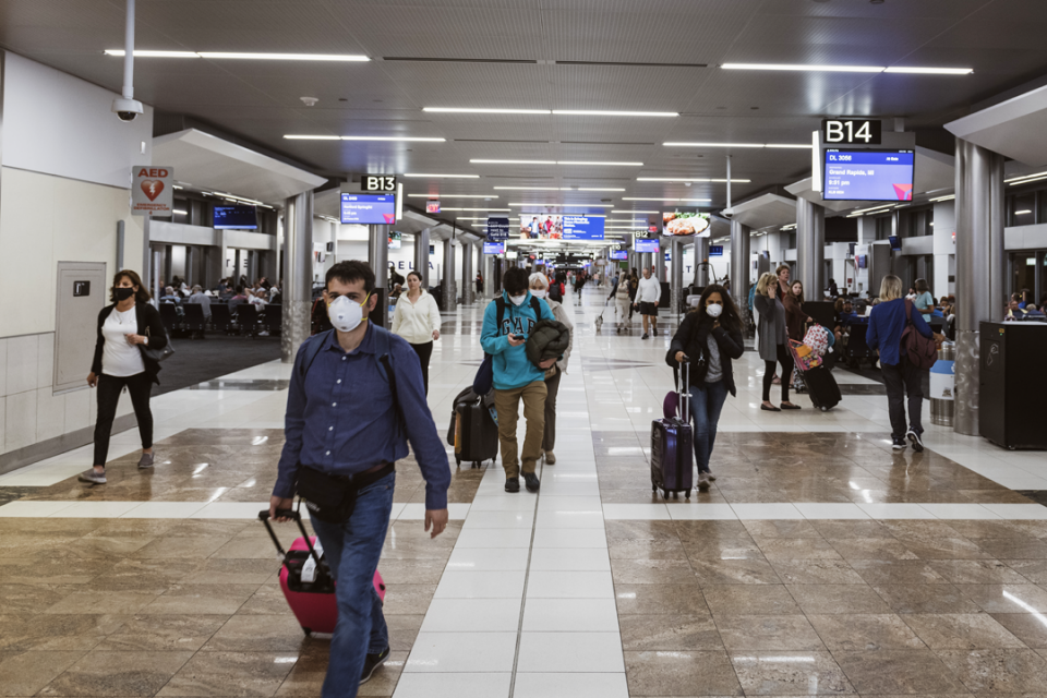 Passengers in an airport terminal traveling during COVID-19 pandemic.