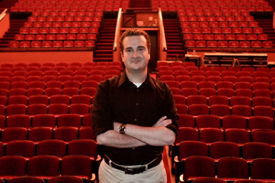 Carl Graci stands in front of empty seats in Lisner Auditorium audience