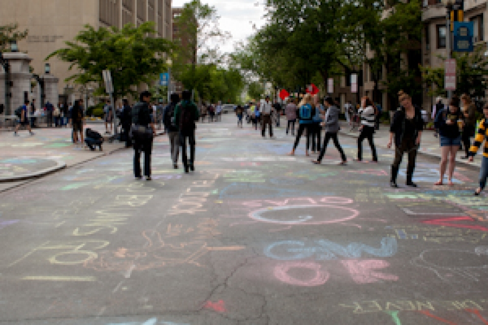 students create art on H Street using chalk while others walk down the street