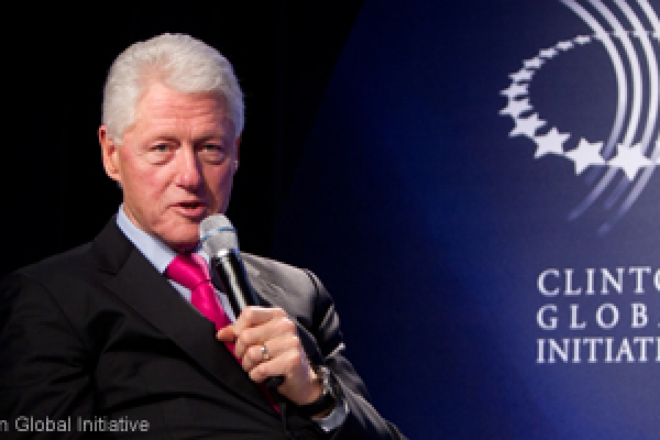 Bill Clinton speaks into microphone with Clinton Global Initiative University banner behind him