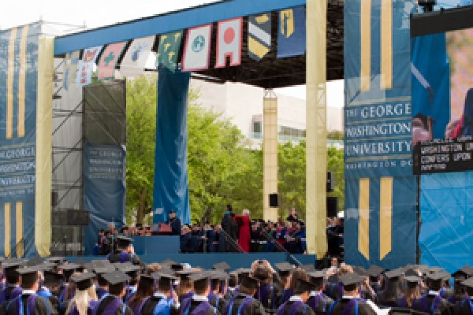Commencement stage on National Mall with Michelle Obama at podium with university community behind her