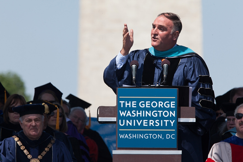 Jose Andres on commencement stage speaking at podium with Washington Monument behind him