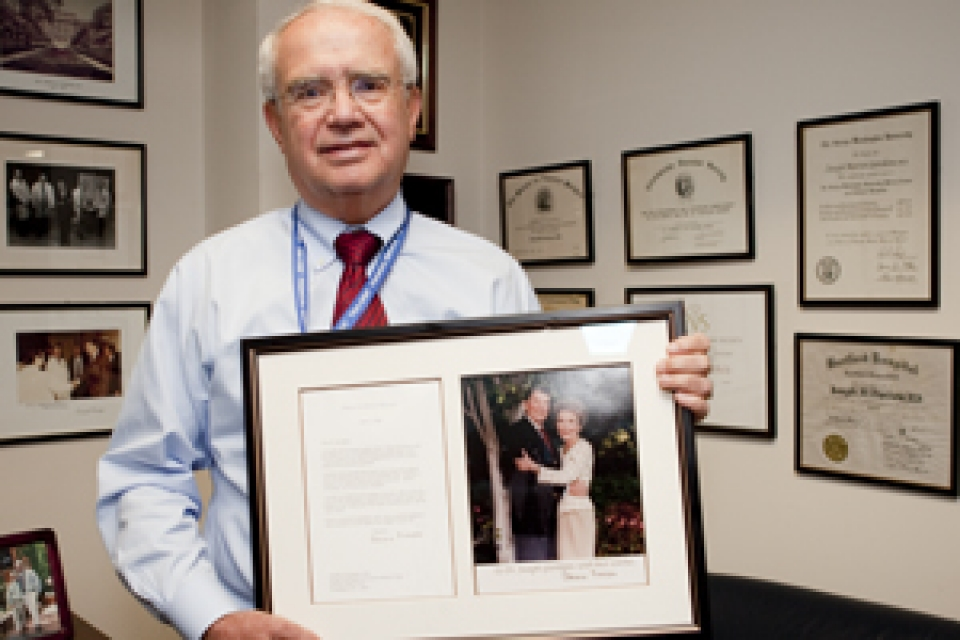 Dr. Joseph Giordano holding framed letter and picture from First Lady Nancy Reagan