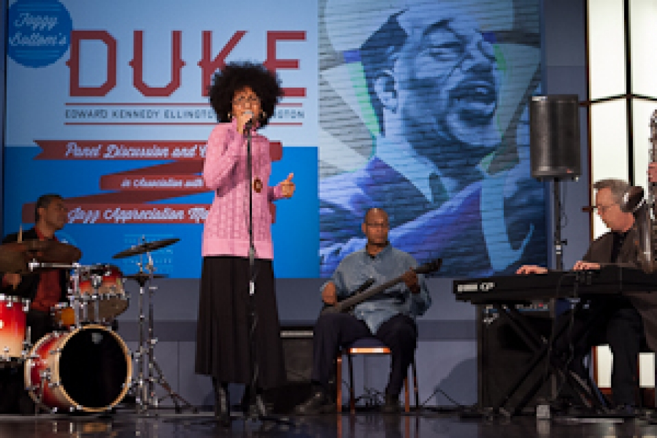 band on stage with woman singing and guitar, saxophone, drum and keyboard players