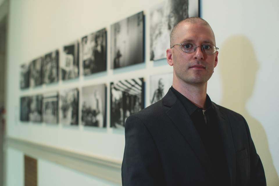Eric Dietrich stands in gallery with his photographs on display behind him