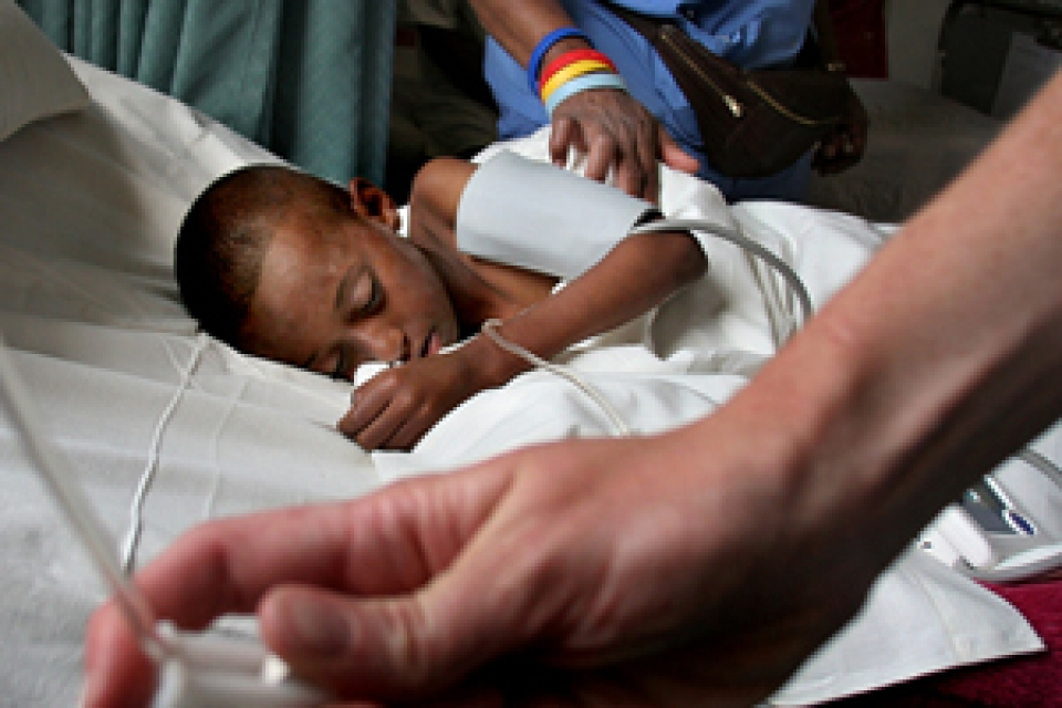 child in hospital bed receiving care