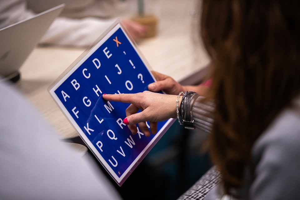 "An autistic young adult in Sean Cleary's ""The Experience of Autism"" class uses an alphabet board to communicate. (Harrison Jones"