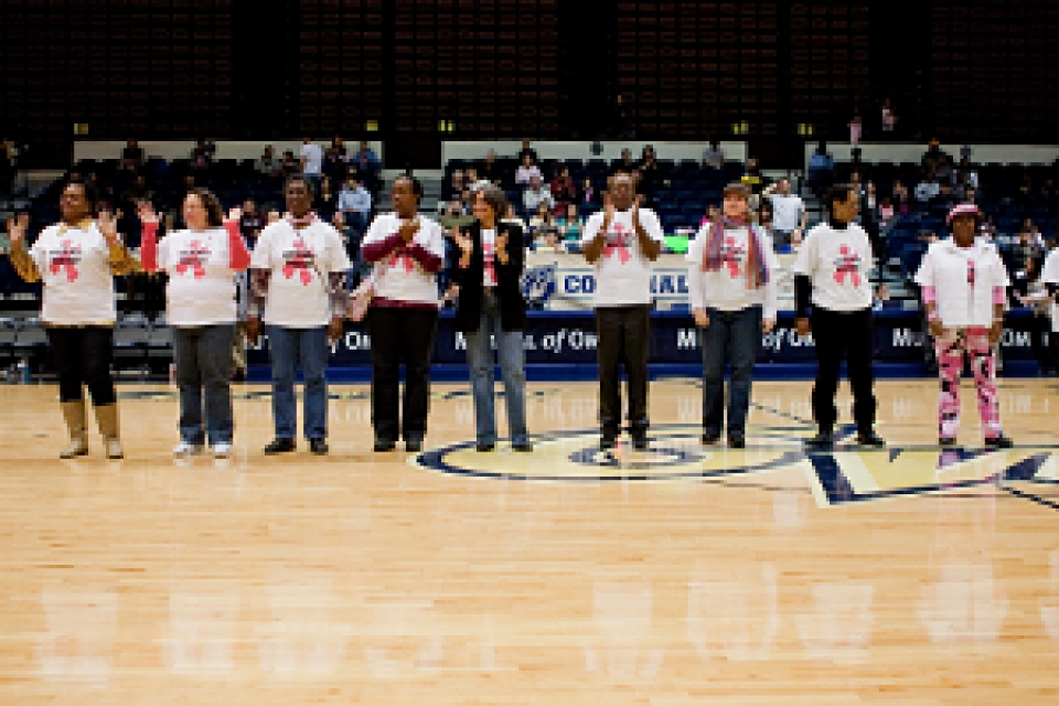members of healing basketball stand on Smith Center court in t shirts with breast cancer ribbon