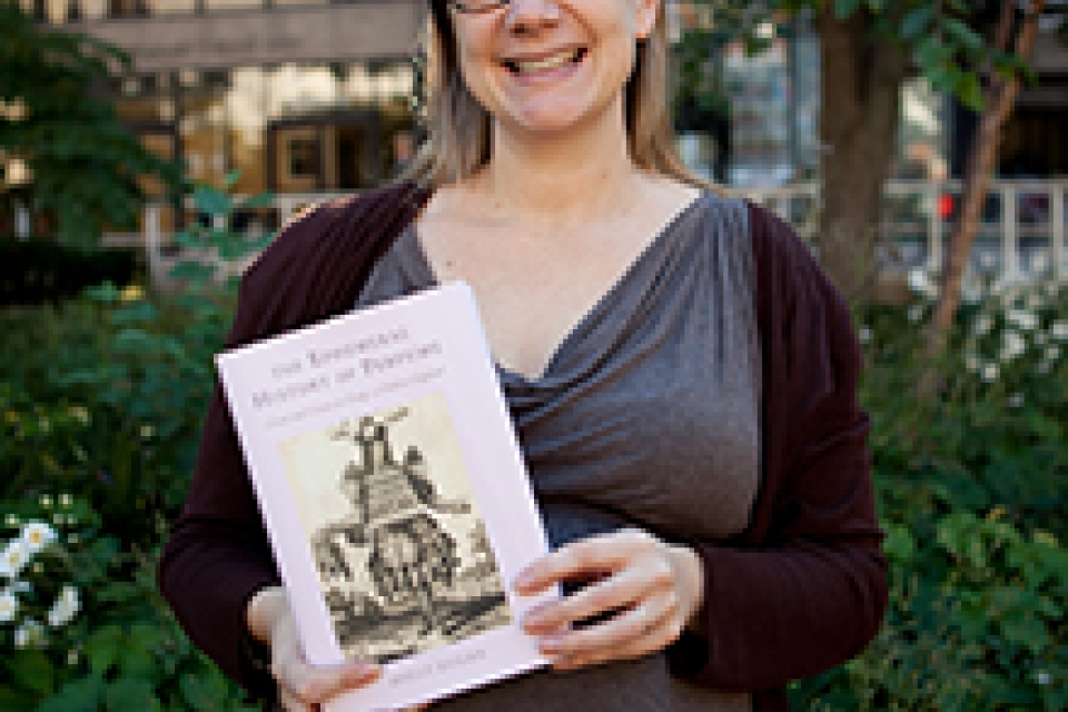 """Holly Dugan holds book and smiles, book is """"The Ephemeral History of Perfume: Scent and Sense in Early Modern England."""""""