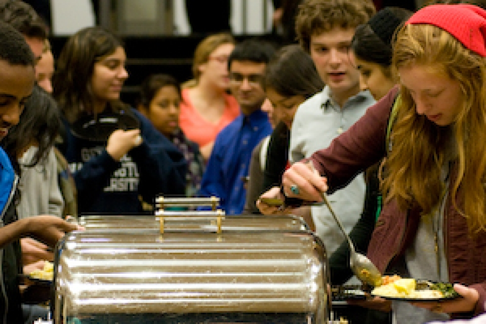 participants at interfaith dinner line up at buffet to get food