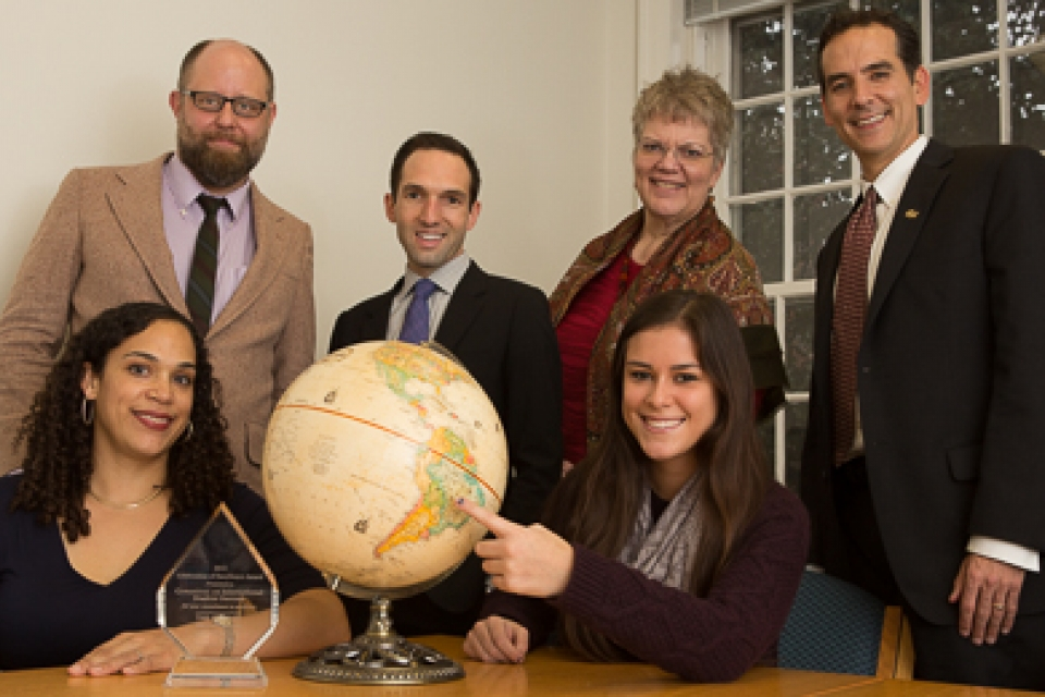 CISS Co-chairs and student liaison sit around table with globe