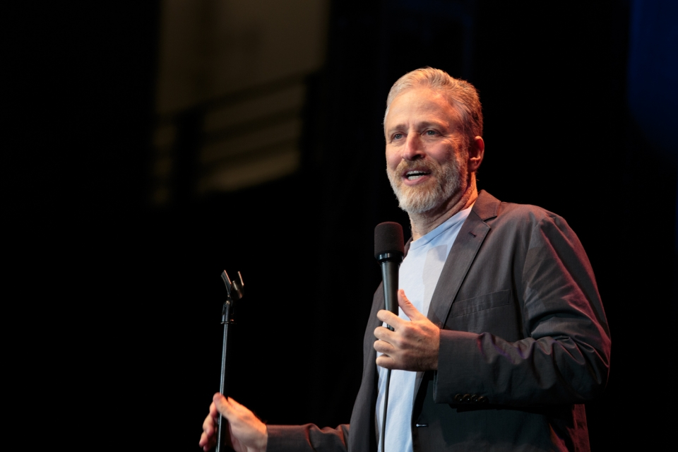Jon Stewart performing standup with microphone in hand