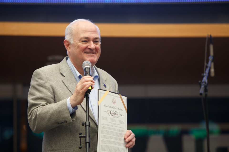 Steven Knapp smiling and speaking into microphone holding paper copy of resolution