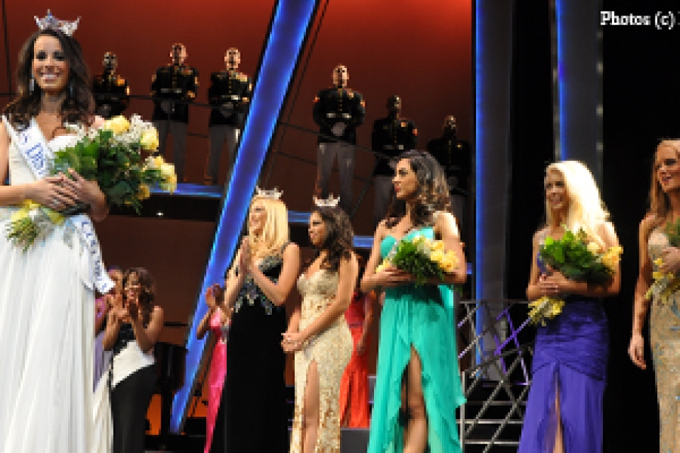 Miss D.C. in crown and ballgown holding flowers with other pageant participants standing behind her