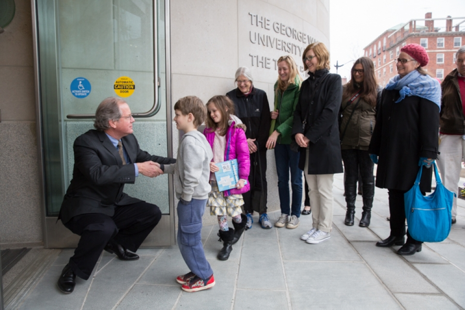 Austin and Lucy Wilson, two children from Alexandria, Va., greet Museum Director John Wetenhall at the new museum opening.