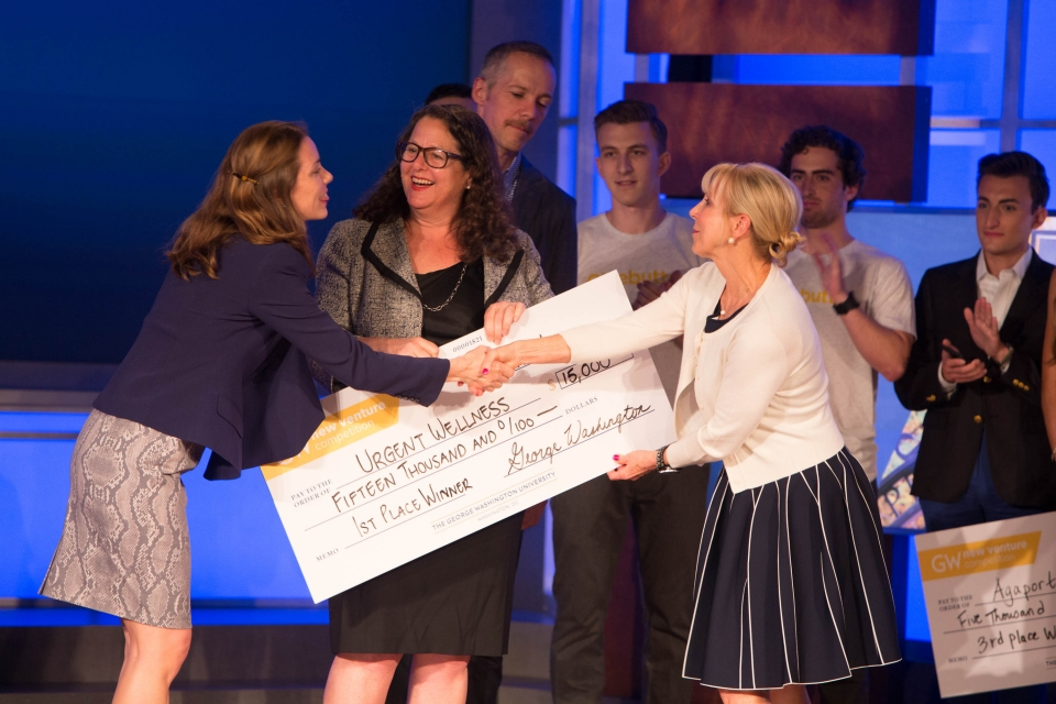 New Venture Competition winner accepts oversized check on stage