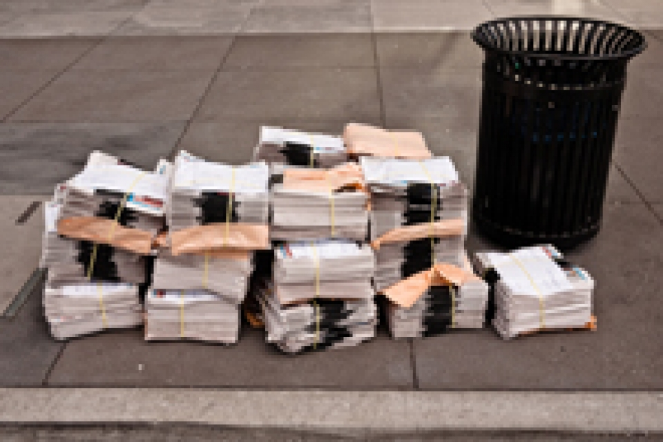 trash can on street with stacks of newspapers next to it