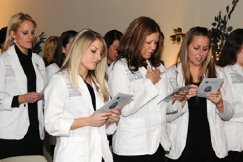 Members of the School of Nursing's first undergraduate class holding papers and received baccalaureate pins,