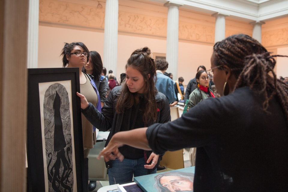 A student receives a critique of her work from a university representative at National Portfolio Day. (William Atkins/GW Today)