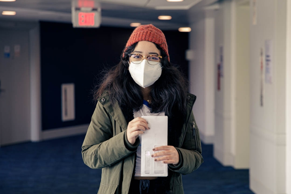 Alejandra Paredes wearing a mask and holding a stack of mail