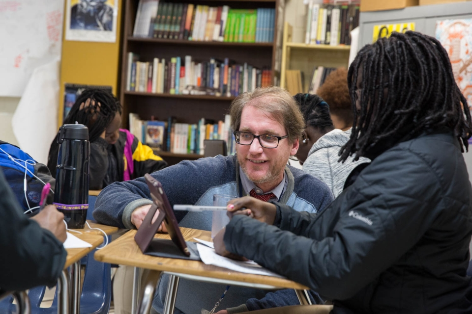 Topher Kandik works with an A.P. English student at the SEED School of Washington, D.C. (Logan Werlinger/GW Today)
