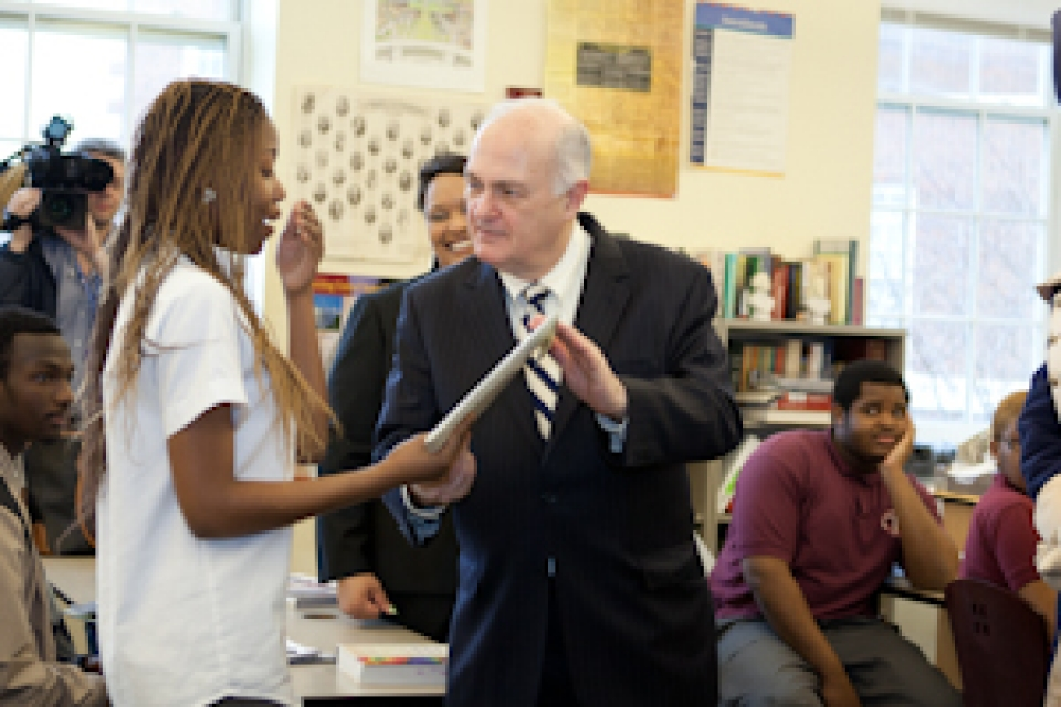 Steven Knap and George mascot surprise female student with SJT scholarship as classmates look on