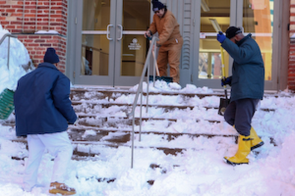 Workers shoveling steps of academic building