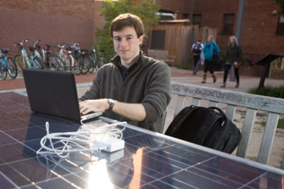 Ben Pryde sits at Solar Table with laptop smiling