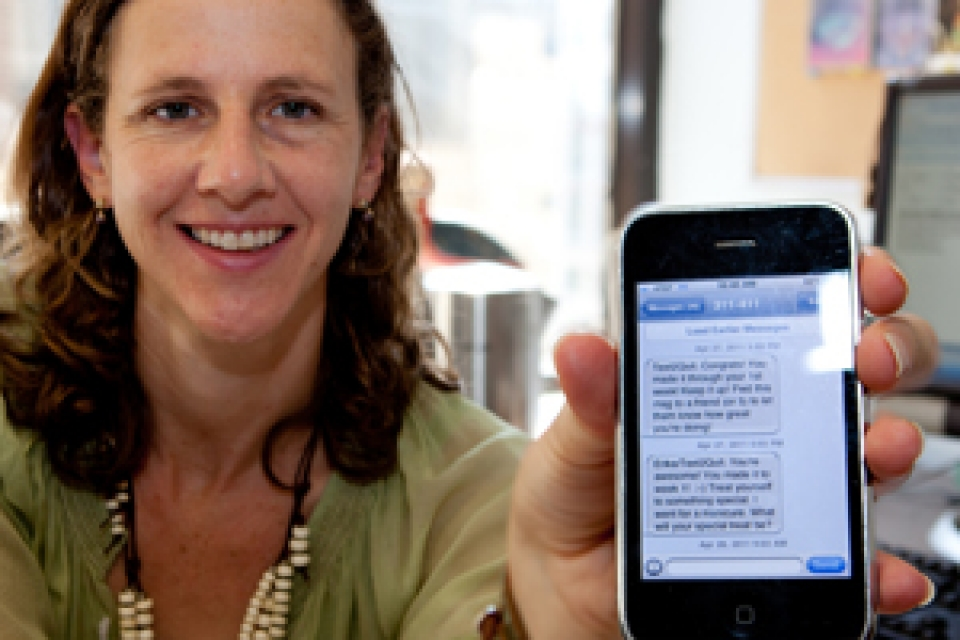 Lorien Abroms holds up iPhone screen with Text2Quit texts on it