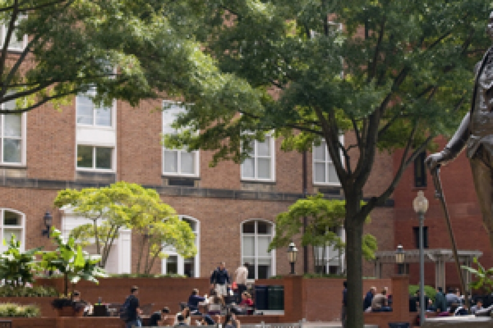 University Yard including George Washington statue and exterior of GW Law building with students gathering outside