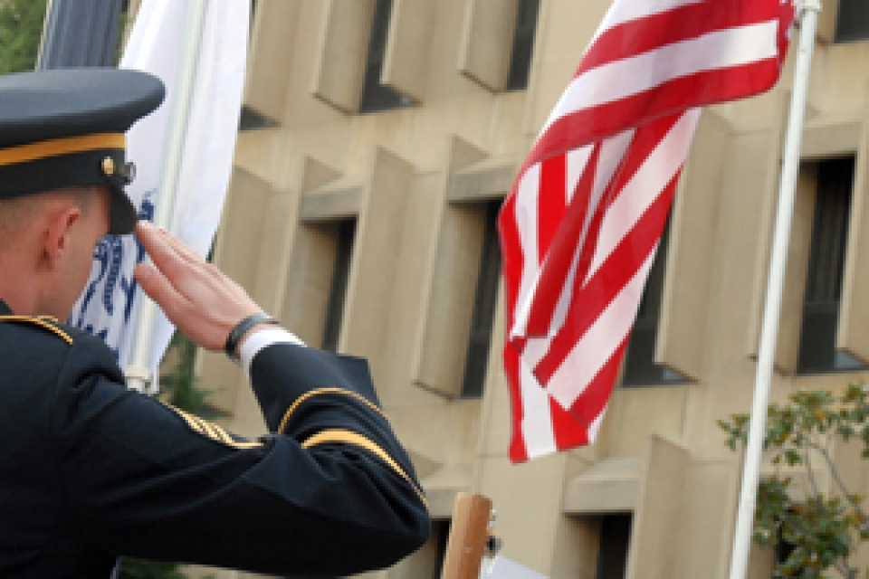 male in military uniform salutes American flag