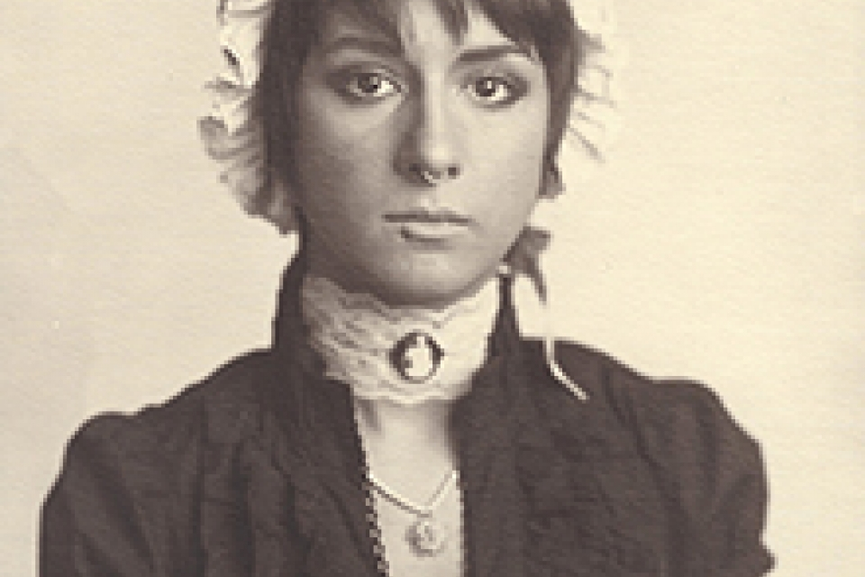 A Belle of Modernity photo, young woman in bonnet, black dress and a neck clothes with nose pierced