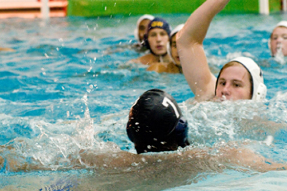 Water polo players in pool with one player holding a ball