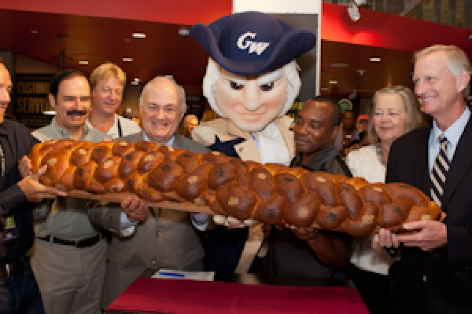 Steven Knapp and mascot George stand with a group with oversized challah roll at Whole Foods opening