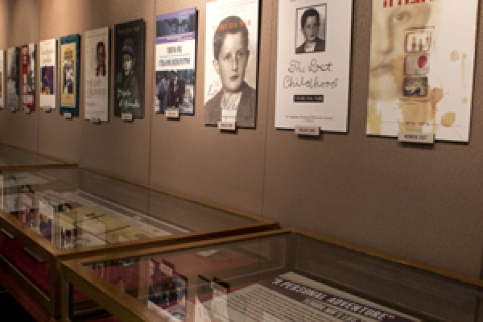 books under glass in exhibit with photographs of book covers lining walls