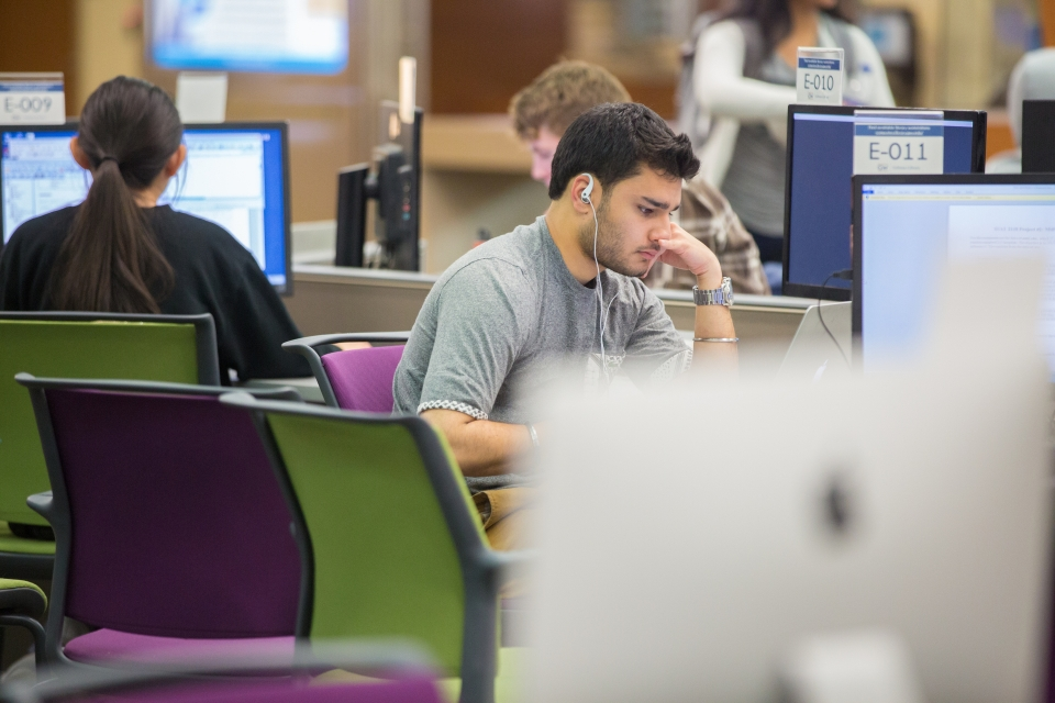 student in library with headphones on reading at desk