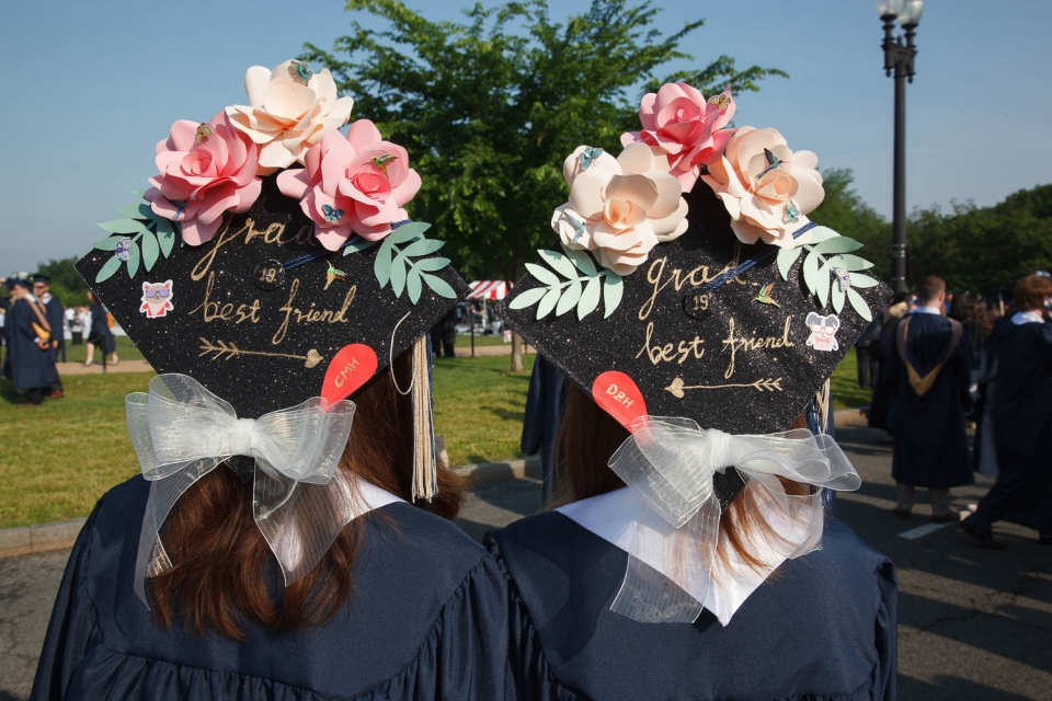 "two students with designed graduation caps ""Best Friend"" with an arrow pointing to the other graduate"