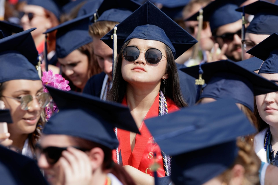 graduate in sunglasses among crowd of graduates