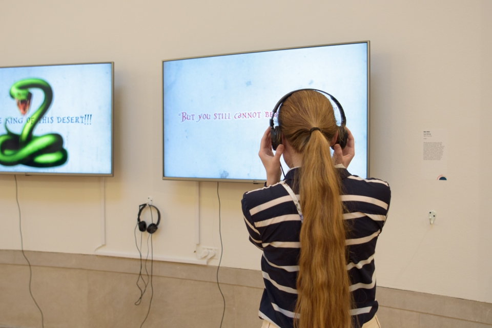 student with headphones on looking at exhibit