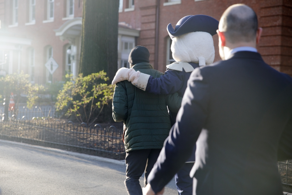 mascot George walks down the street with his arm around a GW community member