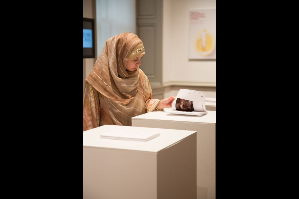 student looking at NEXT brochure on podium