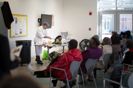 Residents of the community learn about ways to use the produce provided at the market.