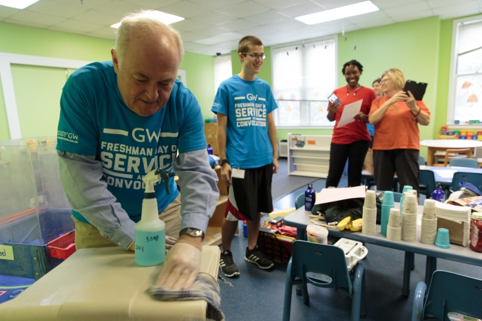 GW President Steven Knapp puts in work at Mazique Childcare Center. (Photo: William Atkins)