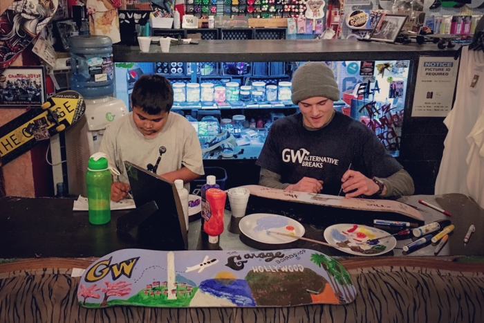 students sit at table working in garage