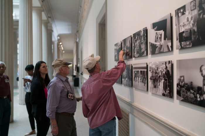 men looking at armed forces photography on walls