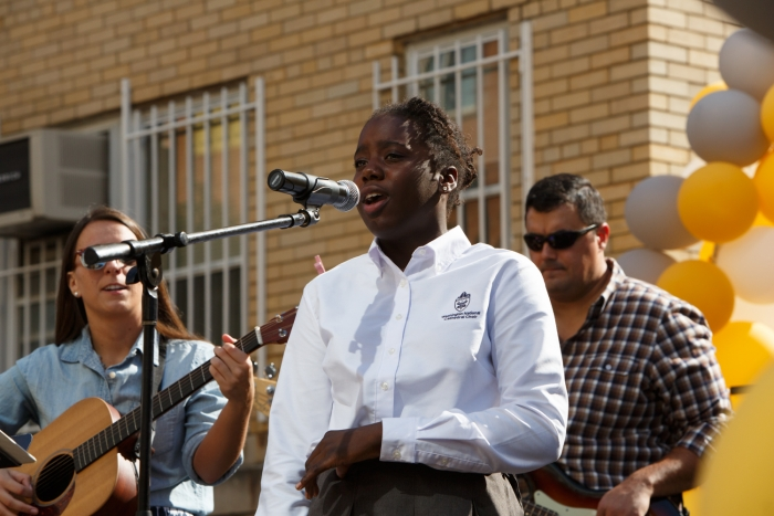 student singing on stage during block party