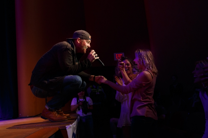 Brett Young holding hand of audience member singing